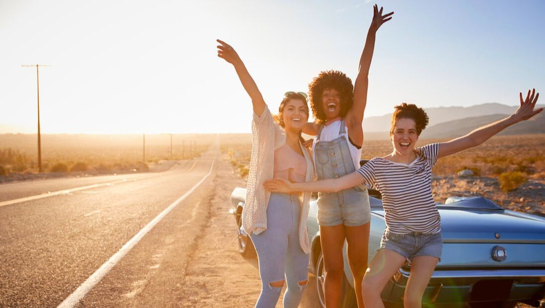 Three women on the side of the highway cheering