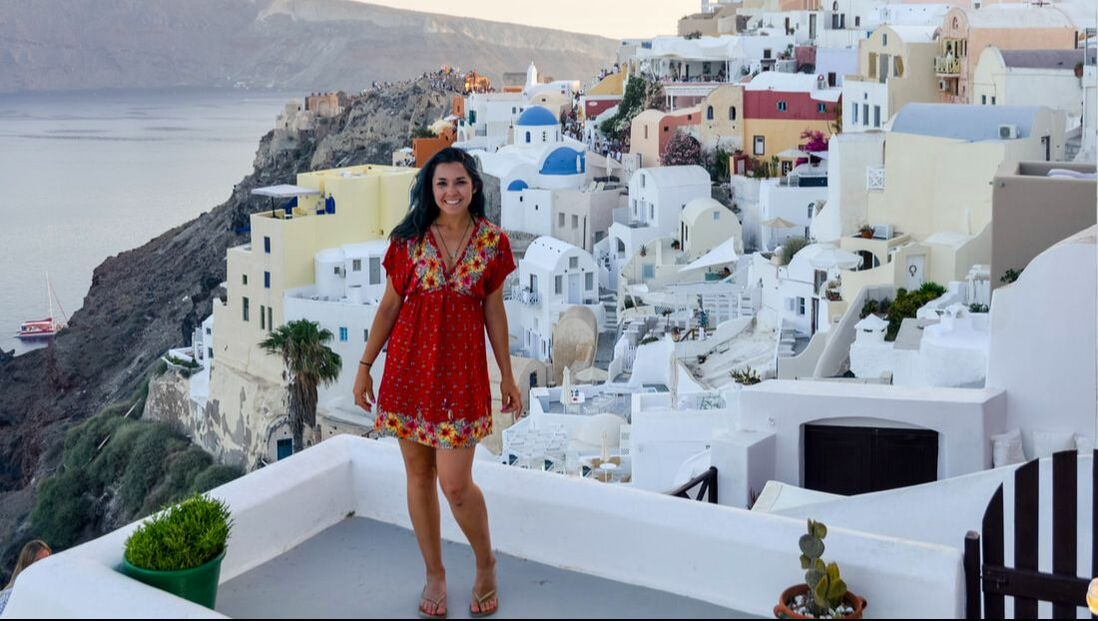 Woman in greece standing on cliff